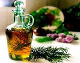 a glass canaster of olive oil and a sprig of rosemary