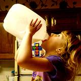 photo of girl drinking milk from gallon jug