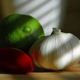 photo of a garlic bulb with a lime and red pepper with emphasis on the benefits of garlic