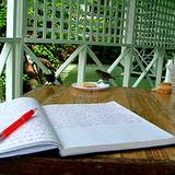 a notebook opened on a table on an outside table